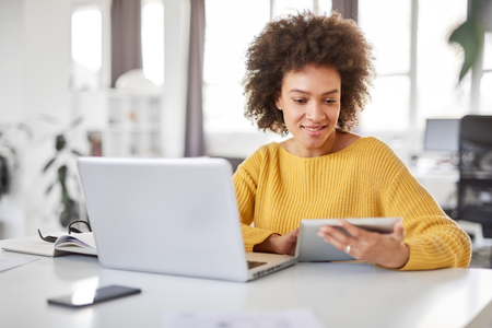 Serious mixed race businesswoman dressed  casual sitting in office and using tablet. Stock Photo - 122301435