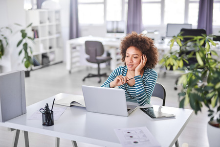 Cute mixed race businesswoman dressed  casual thinking how to solve a problem while sitting in modern office. Stock Photo