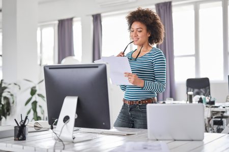 Beautiful smiling mixed race businesswoman dressed casual standing in office and looking at peperwork. Stock Photo - 122301411