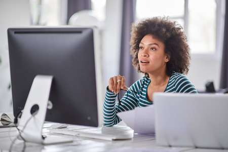 Attractive mixed race businesswoman dressed casual sitting in office, holding paperwork and looking at computer monitor. Stock Photo