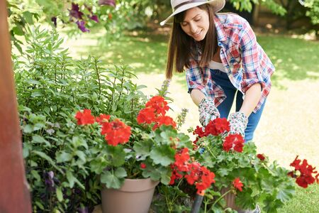 Beautiful smiling Caucasian brunette in working clothes and with hat pruning flowers in her backyard.