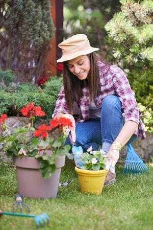 Jardinière caucasienne en vêtements de travail et avec des gants de jardinage plantant du bégonia en s'accroupissant. Extérieur de la cour.