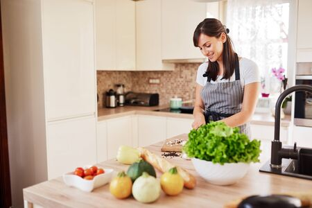 Beautiful smiling dedicated Caucasian brunette in apron standing in kitchen and chopping mushrooms. On table are lots of vegetables. Cooking at home concept. Stock Photo