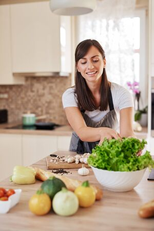 Beautiful hardworking housewife taking salad from bowl while standing in kitchen. Home made dinner preparation concept. Imagens