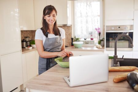 Young Caucasian brunette in apron grating carrots in bowl, preparing dinner and looking at lapotp while standing in kitchen 版權商用圖片