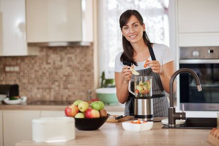 Beautiful Caucasian smiling woman in apron putting vegetables and fruits in blender while standing in kitchen. Standard-Bild