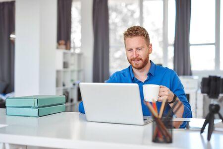 Jonge toegewijde blanke mannelijke werknemer die op kantoor zit, koffie drinkt en een laptop gebruikt. Opstarten bedrijfsconcept. Stockfoto
