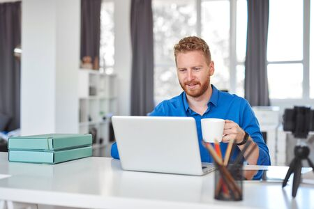Young dedicated Caucasian male employee sitting in office, drinking coffee and using laptop. Start up business concept. Imagens
