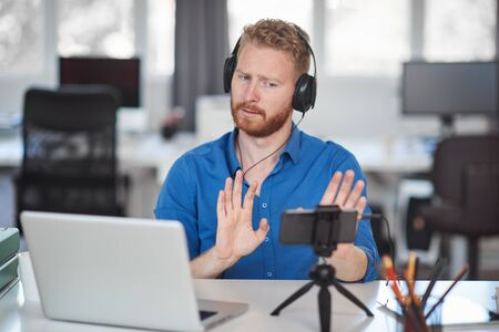 Young Caucasian employee having video call over smart phone while sitting in office. On head are headphones and on desk is laptop and coffee.