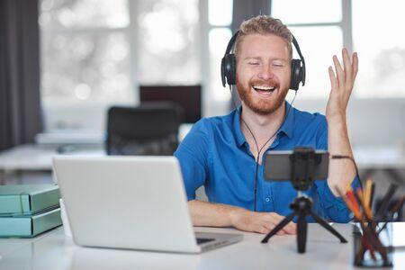 Jonge blanke werknemer met videogesprek via smartphone terwijl hij op kantoor zit. Op het hoofd is een koptelefoon en op het bureau is een laptop en koffie.