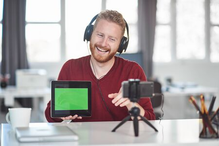 Handsome Caucasian employee having presentation over the internet. In hands is tablet and on head are headphones. Start up business concept.