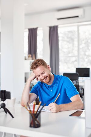 Cheerful Caucasain ginger employee sitting in his office and writing his tasks in notebook.