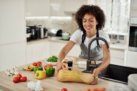 Attractive msixed race woman in paron taking zucchini from kitchen counter. On kitchen counter are lots of vegetables.