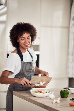 Smiling mixed race woman in apron putting chopped mushrooms in bowl with vegetables. Kitchen interior.