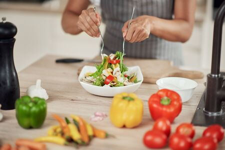 Close up of mixed race woman in apron mixing vegetables in bowl while standing in kitchen at home.
