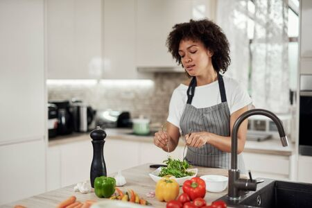 Attractive mixed race woman in apron mixing vegetables in bowl while standing in kitchen at home.