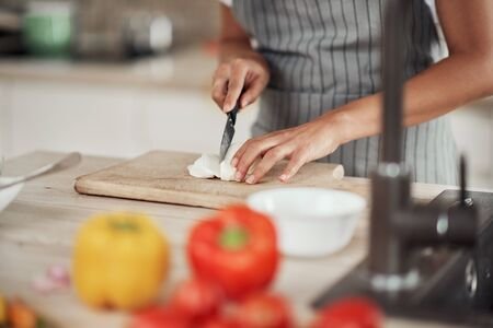 Close up of mixed race woman in apron standing in kitchen and chopping mushrooms. Stok Fotoğraf