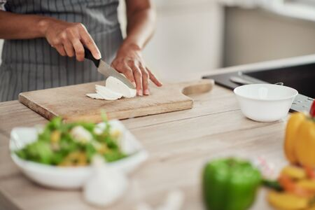 Close up of mixed race woman in apron standing in kitchen and chopping mushrooms. Stock fotó