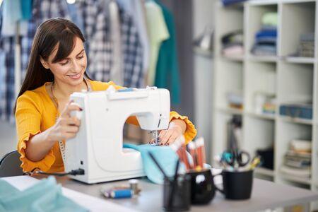 Sonriente a encantadora diseñadora de moda caucásica sentada en su estudio y cosiendo hermoso vestido de noche. Foto de archivo