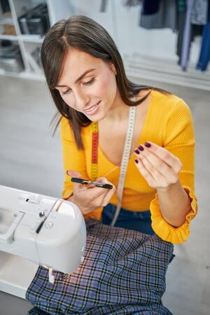 Attractive smiling caucasian brunette sitting in tailoring studio and cutting thread.