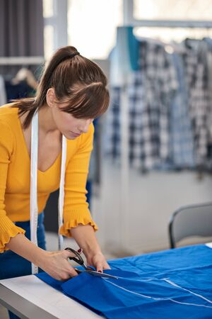 Dedicated seamstress standing next to table and cutting textiles for elegant dress. Фото со стока