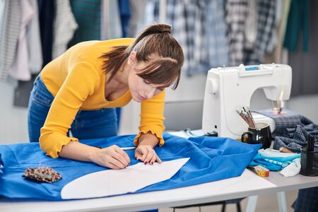 Creative caucasian fashion designer standing in her studio and drawing scheme on blue linen for a beautiful evening dress. Banco de Imagens