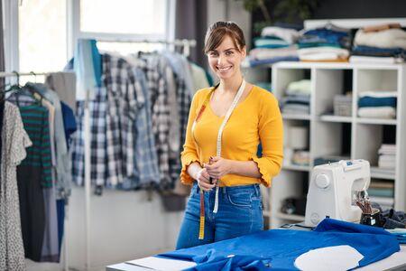 Charmante lächelnde kaukasische Schneiderin, die in ihrem Studio steht und in die Kamera schaut.