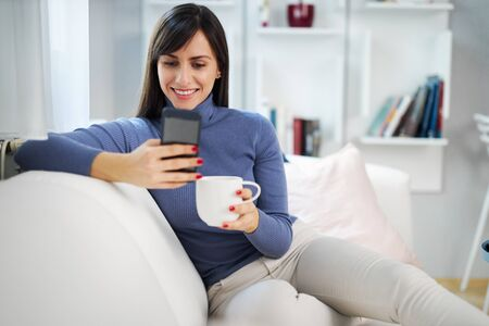 Young attractive smiling brunette sitting on couch in her living room, holding mug with coffee and hanging on social media.