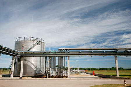 industrial pipelines and storage tank against blue sky photo
