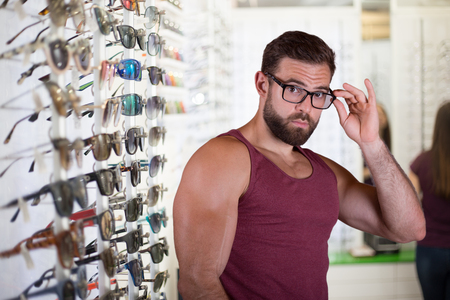 Young man choosing glasses. Optical store