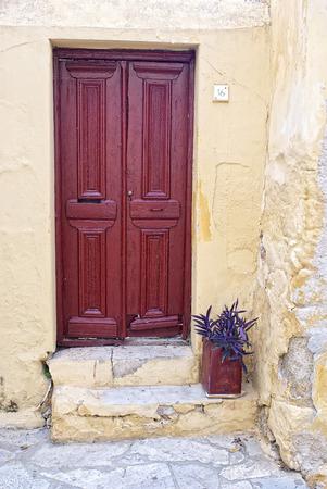 greek pot: Porta e vaso di fiori di una vecchia casa greca. Archivio Fotografico
