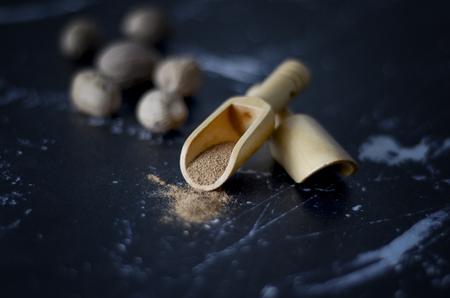 Fresh nutmeg on dark background. Seeds and nutmeg powder Imagens