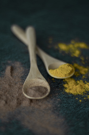 Cinnamon and turmeric powder on green background