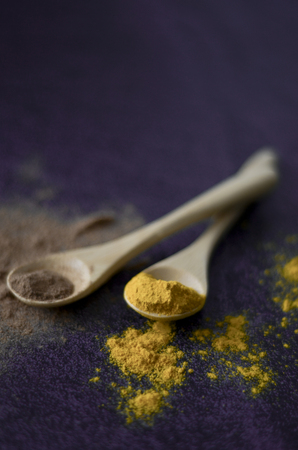 Cinnamon and turmeric powder on purple background. Colorful spices