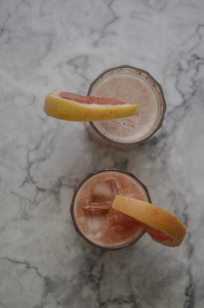 Grapefruit cocktail with gin and tonic. Alchool cocktail or antioxidant healthy beverage. Top view. Glass with ice on marble table.