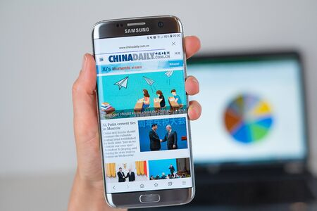 Barcelona / Spain 06 10 2019: China Daily web site on mobile phone screen. Mobile version of China Daily company web page on smartphone. Official web page of China Daily. 報道画像