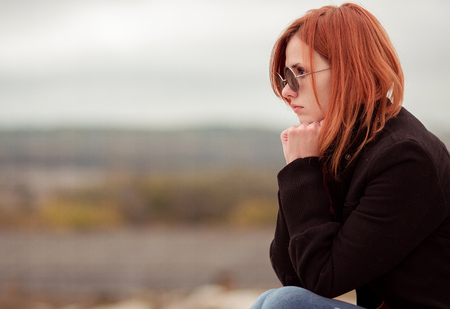 depression: The red-haired girl sits somewhere in mountains and thinks much. Thinker. In sun-protection creative glasses. Stock Photo