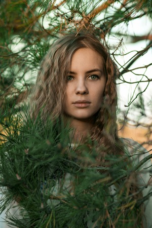 madly: Portrait of madly beautiful girl with huge green eyes and long beautiful hair in greens, trees, flowers, branches. Spring. Summer. Stock Photo