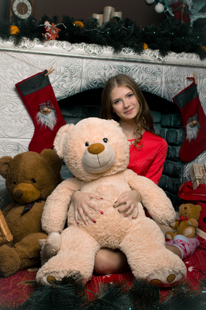 newyears: Very nice, beautiful, long-haired, well-dressed girl with two big bears(white and brown) new-years decoration and fireplace Stock Photo