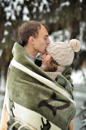 boy smiling: A handsome man kiss on the forehead her beloved, beautiful, pretty girl with sweater, mittens and hut