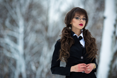 school uniforms: The beautiful teacher, student, teacher, schoolgirl, woman in a suit and a checkered skirt, wearing spectacles also looks is proud forward and it is self-confident Stock Photo