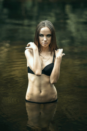 bony: Girl in the water,the girl in a bathing suit,in the sea,river,lake,green.She is thin,bony,skin and bone,gloomy,quiet,serious,not really beautiful,with thin hands.