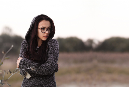 Lonely alone beautiful girl in warm sweater with hood looking aside in autumn field background. Picture of pretty depressed sad unhappy girl with glasses. Alone girl having drug addiction. Lonely girl alone in the world.