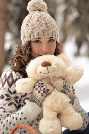 Beautiful, nice, smiling, little and wearing sweater hut and mittens and little girl with a teddy bear in winter forest.Portrait of lovely girl with cute, nice toy.Cute, beautiful, nice girl hug a fluffy, white, beige teddy bear. Girl and bear in winter Stock Photo