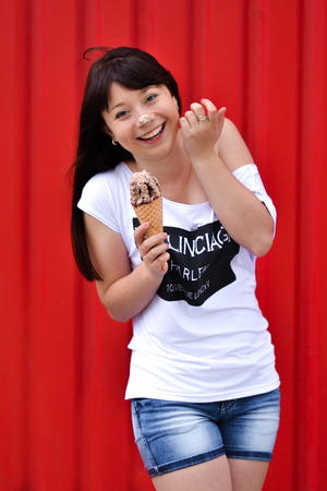 Outdoor closeup fashion portrait of young hipster crazy girl eating ice cream in summer hot weather, having fun and good mood. Picture of laughing smiling happy girl with ice cream on red background. Stock Photo