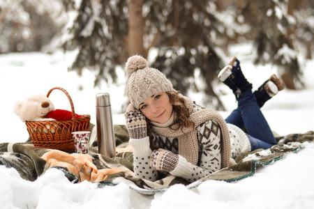 Beautiful,cute,happy,light girl sitting on a blanket in the winter in the cold,snow,fosest,forest and drinking cup of warm tea,background,little,december,january,february,people,child,portrait,year Stock Photo