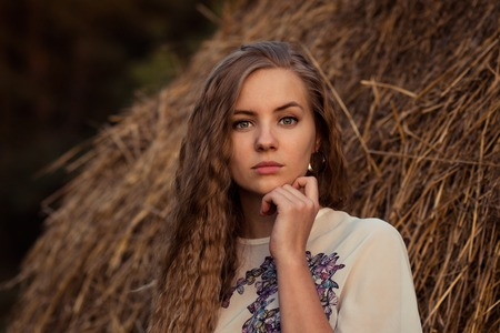 Portrait of very beautiful, attractive, nice, pretty, lovely, cute, serious girl, woman with white transparent blouse, curly long hair, cute face, features near the hay drain. Stock Photo