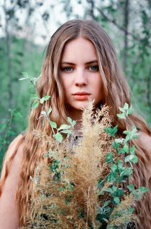 poquito: Realización.Tiempo de primavera.Impresionante, excelente, hermosa, agradable chica con pelo largo, recto, poco rizado con flores al aire libre en verano en verano. Chica imponente, tranquila y seria con rostro serio, mirada, vista con ramo de muchas flores Foto de archivo