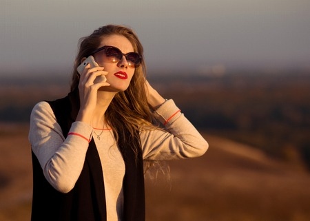 Very beautiful, awesome, beloved, super, pretty, divinely beautiful, with new, original, fine, beautiful sunglasses, red lips speaks by phone, discusses, communicates, expresses opinion, gives advice at sunset, nice, adorable, attracive, pretty,style