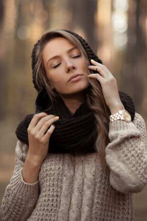 Fashionable, posing, stunning, attractive and very sensual, beautiful girl with closed elegant finders near the perfect face, pure skin.Inspiring, admiring, sensual, lovely, beautiful attractive girl in warm sweater and scarf in autum forest Stock Photo